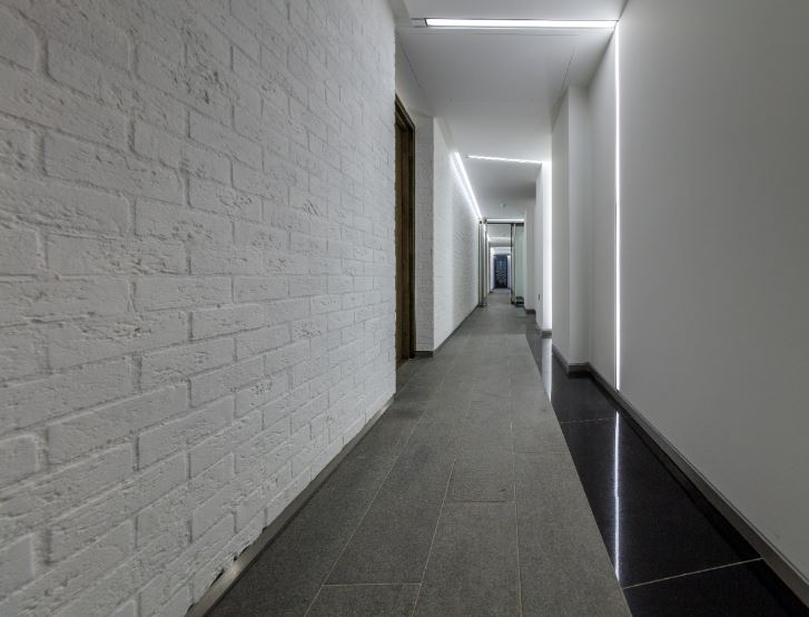 corridor with white brick wall and natural stone floor