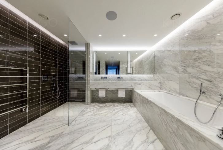 marble bathroom with walk in shower and marble bath