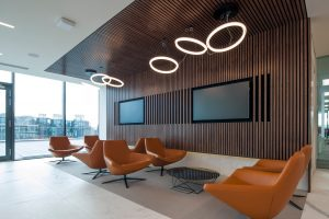 orange armchairs in wooden paneled area with ring lights