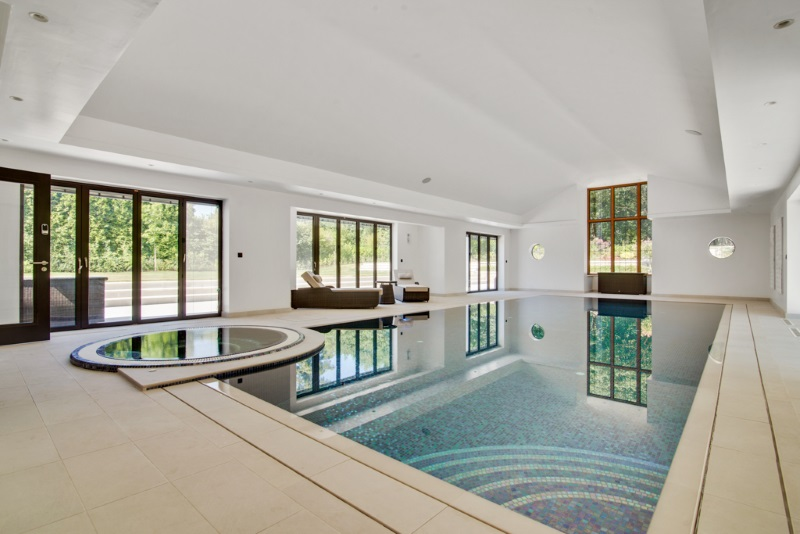 pool with jacuzzi and tall white ceilings and big windows