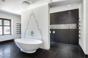 bath against feature wall and walk in shower behind